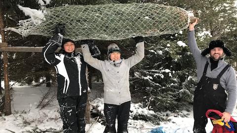 Les jeunes tiennent leur sapin à bout de bras dans la forêt du secteur Cléricy de Rouyn-Noranda.