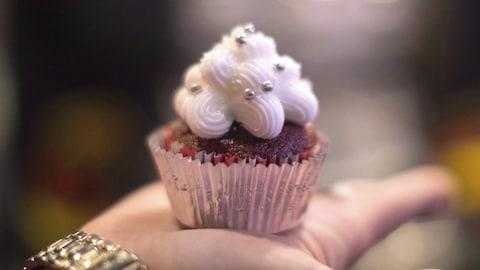 Un petit gâteau au cannabis placé dans un papier aluminium et décoré d'un glaçage à la vanille est dans la paume d'une main.