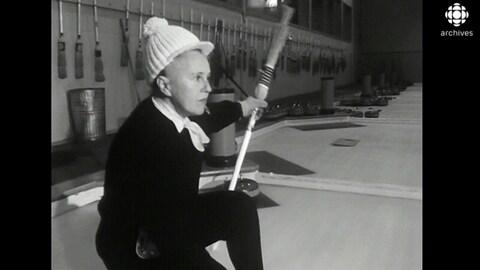 Femme qui tient son balai, accroupie, prête à lancer sa pierre.