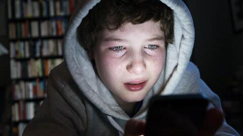 Un garçon consulte son téléphone.