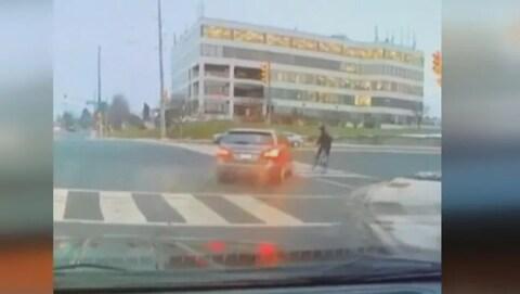 Une capture d'écran avec une voiture et un cycliste dans une intersection.