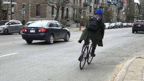 Une cycliste sur la rue Sherbrooke où il n'y a ni piste ni bande cyclable. Jusqu'à 3400 cyclistes y roulent chaque jour.