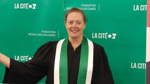 Une jeune dame habillée d'une toge devant une banderole portant le logo du collège La Cité, à Ottawa.