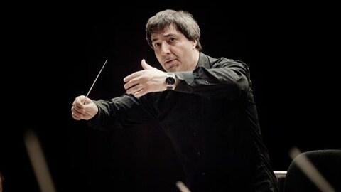 Daniel Raiskin dirige un orchestre à l'aide de mouvements de mains.