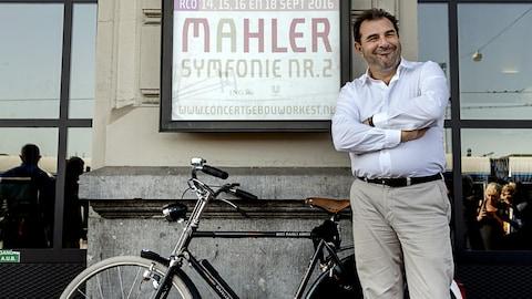 Le chef d'orchestre Daniele Gatti croise les bras devant une affiche en son honneur et prend la pose avec un vélo à gauche.