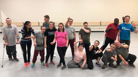 Les danseurs posent en groupe dans le studio de danse.