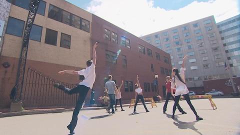 6 danseurs de dos, dans les rues d'une grande ville.