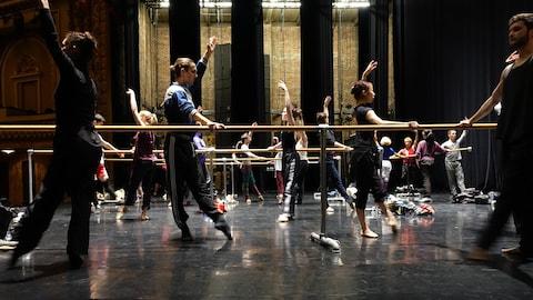 Des danseurs font des exercices à la barre.