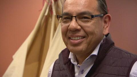 Daren Keewatin apparaît avec ses lunettes en gros plan, avec une chemise fuschia et un large sourire.