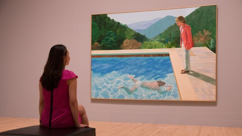 Une femme de dos est assise et regarde le tableau de David Hockney «Portrait of an Artist (Pool with Two Figures)» accroché à un mur.