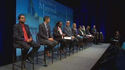 Huit personnes assises sur des chaises hautes, sur un podium.