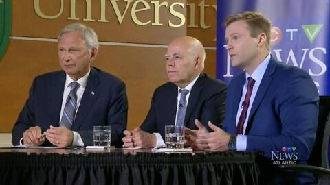 Les trois hommes assis à la même table sur le plateau de tournage