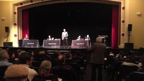 Un homme pose une question à un candidat debout sur la scène, avec trois autres candidats à ses côtés.