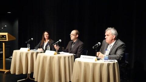 Les trois candidats, deux hommes, une femme, à la préfecture de la MRC de la Haute-Gaspésie sont assis chacun à une table sur laquelle est posé un micro.