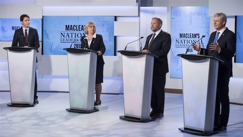 Trois hommes et une femme derrière des lutrins sur un plateau de télévision pour un débat.