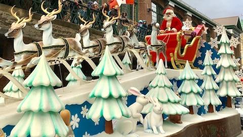 Un père Noël sur un char allégorique avec des faux rennes devant une foule.