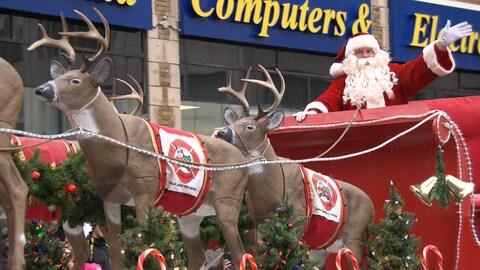 Le père Noël dans son char allégorique salue la foule.