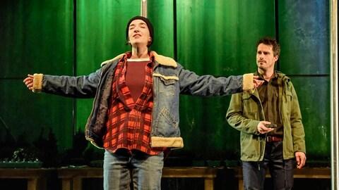 Une actrice se tient debout avec les bras ouverts, un acteur derrière elle la fixe.