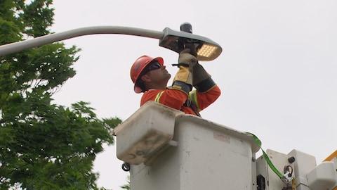 Un travailleur installe un lampadaire au DEL.