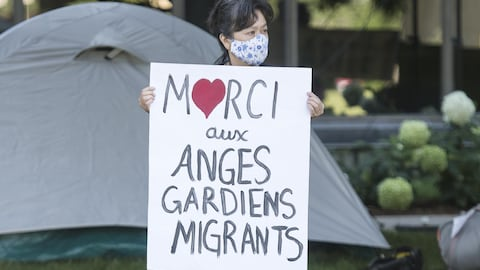 Une manifestante avec un panneau remerciant les anges gardiens.