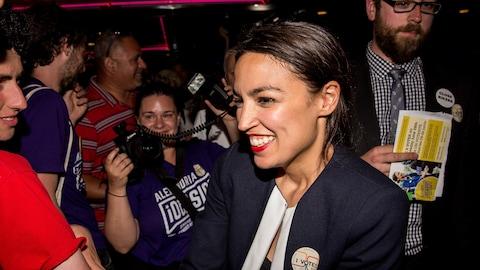 Une femme au large sourire serre des mains dans une foule.