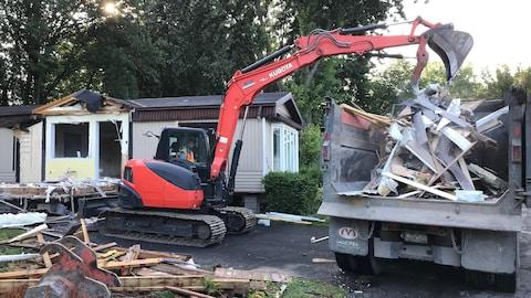 Une pelle mécanique démolit une maison mobile.