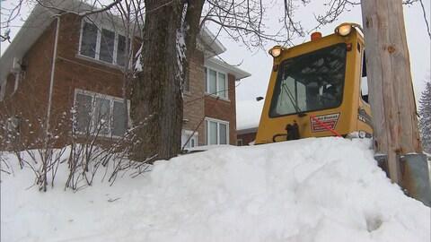 Un tracteur déblaie un trottoir à Trois-Rivières.
