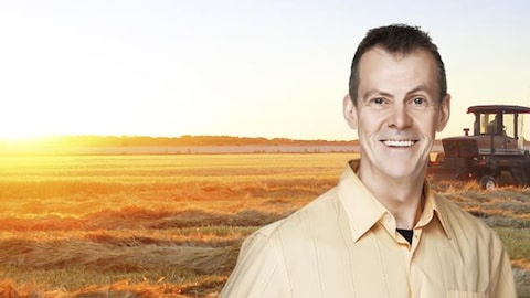 Denis Chamberland souriant devant un champ de blé moissonné