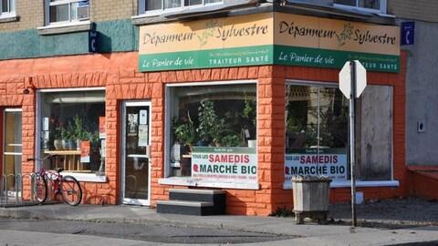 Un commerce peint en orange est situé sur le coin d'une rue