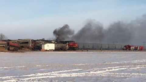 La fumée s'échappe des wagons abîmés du train, deux camions de pompiers s'approchent du train.