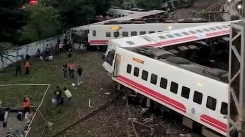 Plan panoramique du train de plusieurs voitures ayant quitté la voie ferrée.