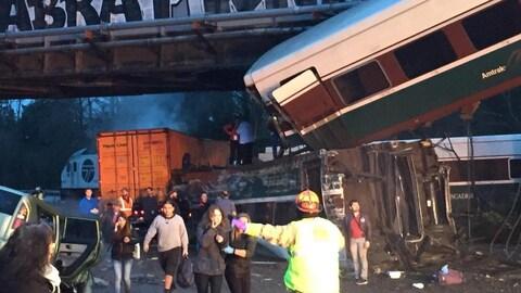 Des gens fuient les lieux d'un accident de train avec les services d'urgence sur la route.