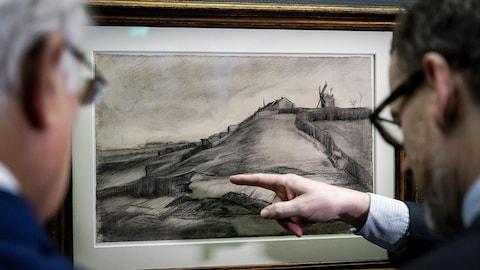 Deux hommes regardent un dessin en noir et blanc représentant une colline au sommet de laquelle se trouvent un moulin et de petites maisons.