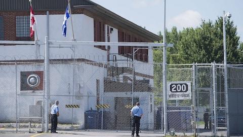 Des gardes se tiennent à l'extérieur des portes du centre de détention pour immigrants à Laval.