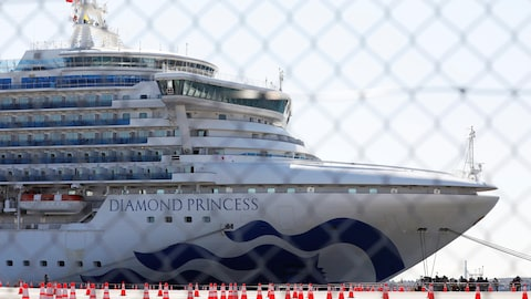 Le navire de croisière Diamond Princess vu à travers une clôture en acier