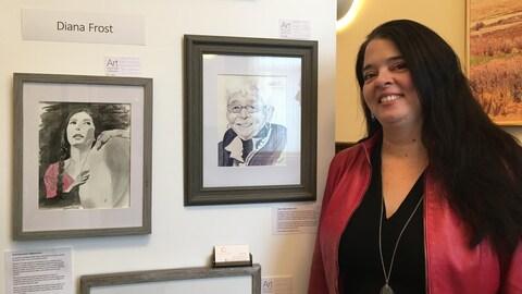 Diana Frost pose devant les deux portraits de Daphne Odjig et Alanis Obomsawin, des oeuvres au fusain et à l'encre.