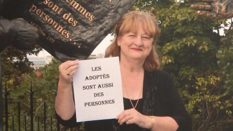 Une femme aux cheveux roux brandit une pancarte sur laquelle on peut lire : les adoptés sont aussi des personnes.