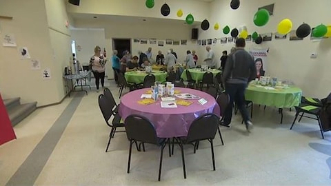 Une salle communautaire avec des gens à table