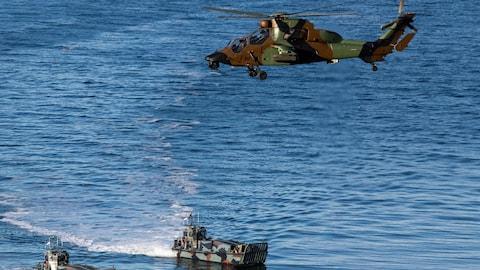 Un hélicoptère vole au-dessus de deux bateaux.