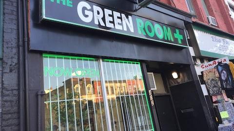 L'entrée du point de vente de cannabis The Green Room, à Toronto. Le nom est écrit en lettres blanches et vertes. Dans la vitrine, on peut lire « maintenant ouvert ».