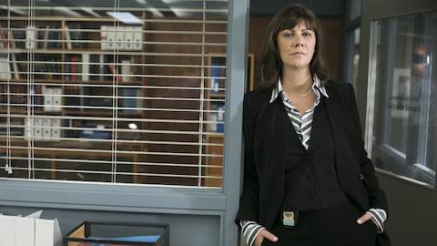 Geneviève Brouillette pose dans le commissariat, adossée à un cadre de porte.