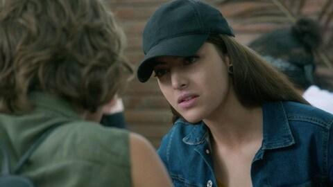 Une jeune femme qui porte une casquette parle avec une personne assise en face d'elle.