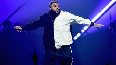 DJ Khaled est sur scène et écarte les bras.