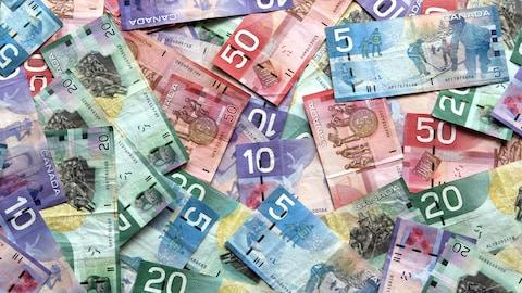 Des dollars canadiens de valeurs variées en tas.