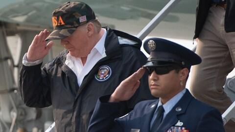 Donald Trump descend d'un avion et fait un salut militaire, vêtu d'une casquette.
