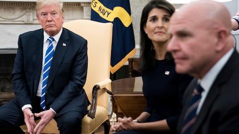 Donald Trump, assis dans une chaise dans le bureau ovale, avec Nikki Haley et H. R. McMaster.