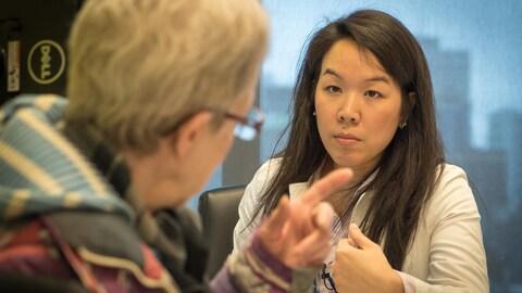 Dorice Khamla écoute une patiente dans son bureau.