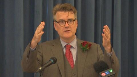 Dougal Lamont, en costume trois-pièces, lève les deux bras devant lui alors qu'il s'exprime devant un micro.