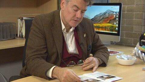 Dougald Lamont assis à son bureau, face à sa brochure.