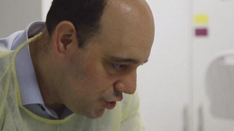 Un docteur, avec une jaquette protectrice jeune, parle à un patient, hors du cadre de la photo.